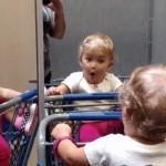 三面鏡に映る自分の姿を不思議そうに覗き込む赤ちゃん