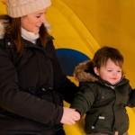 滑り台で遊ぶ息子に付き添う母親と父親の接し方の違いが分かる写真
