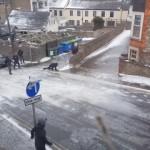 路面が凍結した住宅街を歩いて移動しようとする人々のシュールな光景