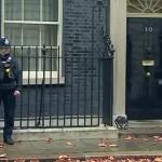 「早くドアをノックしにゃさい!」と警備の警察官に目で促すイギリス首相官邸ネズミ捕獲長のラリーくん