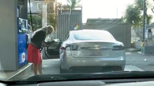 電気自動車にガソリンを給油しようとするも、給油口が見つからず困惑するお姉さん