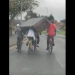 見事なチームワークで重いソファを運ぶサイクリストの4人組