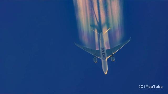 鮮やかな虹色の飛行機雲を引きながら飛行する航空機