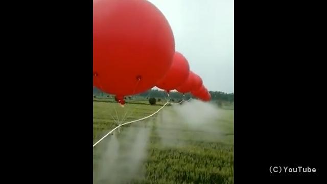 風船を使って効率よく畑に農薬を散布する中国の農村風景